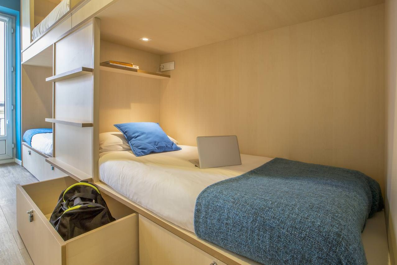 Mola Hostel Madrid single bed in shared dormitory with security drawers below