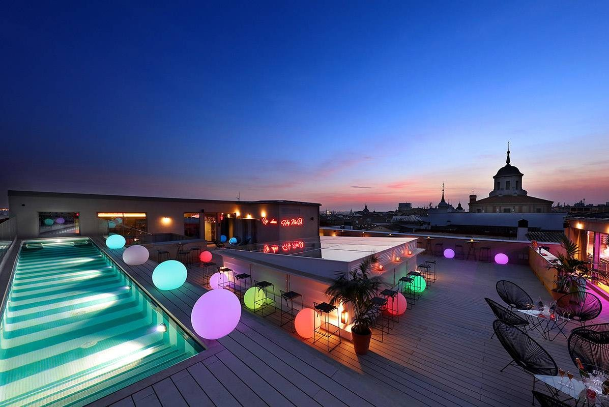 Axel Hotel Madrid terrace rooftop with sky bar lounge party and cocktails with sunset city skyline